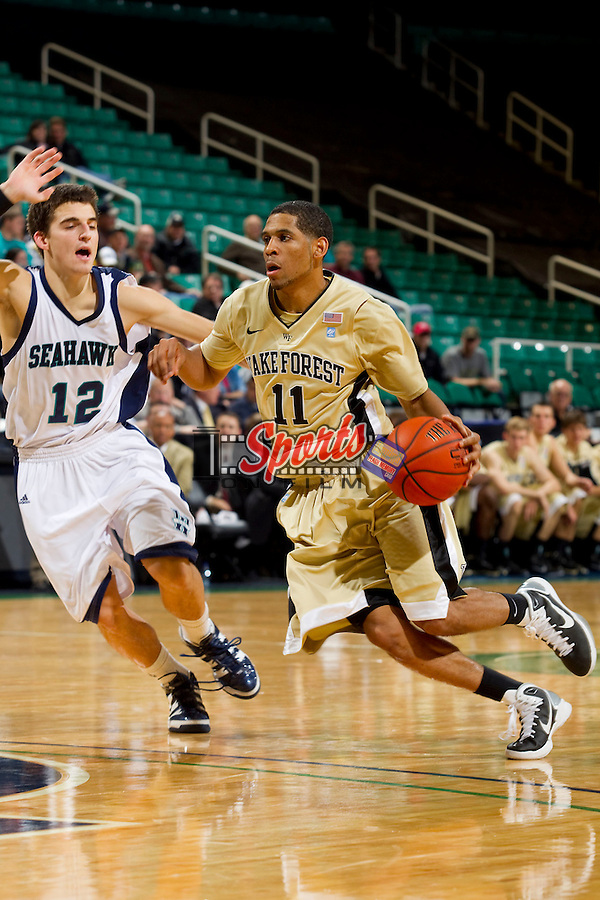 C.J. Harris #11 of the Wake Forest Demon Deacons drives the lane past Tanner Milson #12 of the UNC-Wilmington Seahawks at the Greensboro Coliseum on December 12, 2010 in Greensboro, North Carolina.  The Seahawks defeated the Demon Deacons 81-69. Photo by Brian Westerholt / Sports On Film