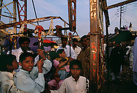 Children wait outside for the gates to be opened for them to come in to see the circus. The celebration is part of a camel mela in the desert.