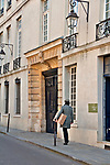 Man carrying a box walks down a street in the historic district of Le Marais in Paris, France