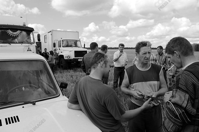 Alexander Almazov, deputy director of Agro-Invest at their holding at Stanovoye, Lipetsk region, gave out intructions as they brought in the wheat harvest and some drivers admired a knife. Russia, July 30, 2008.