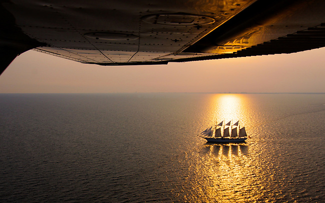 Silhouetted Tall ship sailing south from Pensacola Bay while being back lighted by setting sun.  Aerial photo- 600 ft AGL