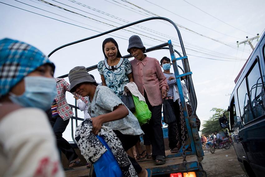 Garment workers head to work in the backs of trucks in Phnom Penh, Cambodia, September 8, 2010.