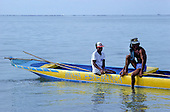 "Itaparica Island, Bahia, Brazil. Two fishermen looking relaxed in a yellow and blued dugout canoe ""Minha Esperanca""."