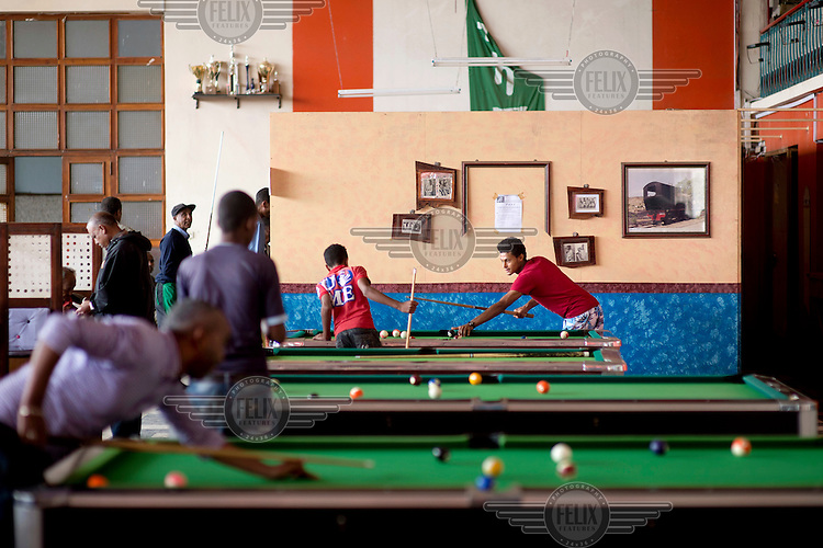Young men playing billards inside the Multi Sport Club. They play a form of five-pin billiards, originally an Italian billiards game.