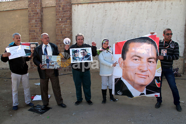 Supporters of former Egyptian president Hosni Mubarak hold his poster outside the police academy in Cairo, Egypt, Jan. 12, 2014. Ousted Egyptian leader Hosni Mubarak's last prime minister, Ahmed Shafik, said in a television interview broadcast on Thursday that he would run for president if the army chief does not contest elections. Photo by Mohammed Bendari