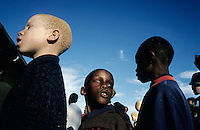 KLIPRIVER, SOUTH AFRICA APRIL 15: Sibonelo Mazibuko, age 7, Windy Matila, age 9, and.Judith Hlongwane, age 11, stands on a line singing songs before a new school day starts, early in the morning on April 15, 2003 at Sibonile (means: we have seen) School for the Blind in Klipriver, south of Johannesburg, South Africa. A blind woman founded the school in 1994. The school has about 125 students from disadvantaged communities around South Africa. Many of the children have faced rejection from their families and communities, and at Sibonile they have a chance for a good education. .(Photo: Per-Anders Pettersson)..