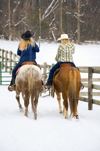 Two horse women friends out horseback riding in scenic winter falling snow, young adult country girl companions, western style clothing and cowboy hats,  rural Pennsylvania, PA, USA.