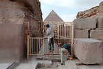 CAIRO - NOVEMBER 30, 2004 : Maintenance crews repair the fence as hordes of foreign and egyptian tourists visit the 5000 years old Giza pyramids in Cairo, on November 30, 2004. Situated high on a desert plateau overlooking sprawling Cairo, Giza is the most visited tourist site in Egypt ,with the Sphinx and the 481ft high great Pyramid. Tourism has been on the decline in Egypt following a series of terrorist attacks targeting foreign tourists. (Photo by Jean-Marc Giboux)