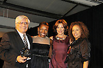 """Bill Solli is presented the Hearts of Gold Humanitarian Award by Countess LuAnn - L to R -  Deb Koenigsberger -Countess LuAnn de Lesseps -  Tamara Tunie at The Fourteenth Annual Hearts of Gold Gala """"Hooray for Hollywood!"""" - with its mission to foster sustainable change in lifestyle and levels of self-sufficiency for homeless mothers and their children on October 28, 2010 at the Metropolitan Pavillion, New York City, New York. (Photo by Sue Coflin/Max Photos)"""