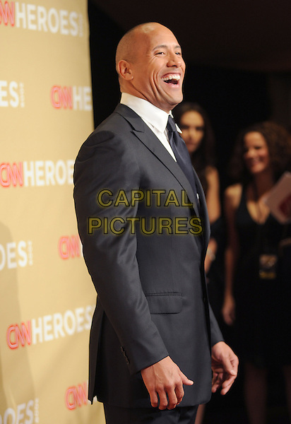 """DWAYNE """"THE ROCK"""" JOHNSON.at The 3rd Annual CNN Heroes: An All-Star Tribute held at The Kodak Theatre in Hollywood, California, USA,  November 21st 2009                                                                   .half length grey gray suit side profile mouth open laughing funny black .CAP/RKE/DVS.©DVS/RockinExposures/Capital Pictures"""