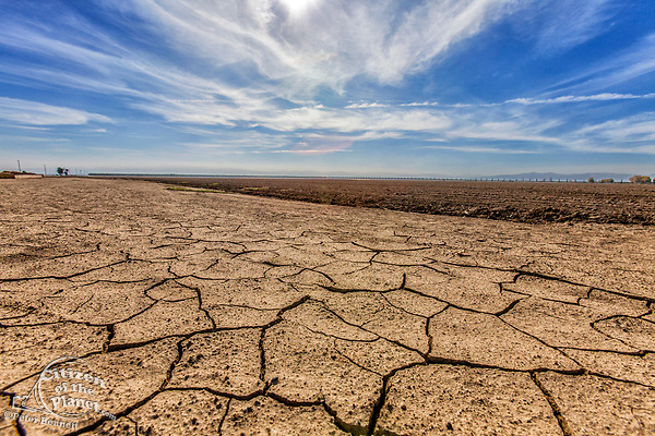 Cracked and dry earth next to fallow crop field. Fresno County, San Joachin Valley, California, USA