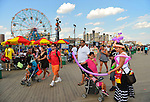 Brooklyn, New York, USA. 10th August 2013.  IVELIZ BALTAZAR, from Harrison, New Jersey, wears a colorful balloon hat and apron, as she creates balloon shapes for a toddler girl, during the 3rd Annual Coney Island History Day celebration. Children get the balloons for free that Baltazar creates when she visits the world famous boardwalk along the beach,