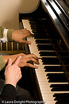 Middle School grade 8 music education closeup of teacher's hand and male student's hands at piano keyboard vertical