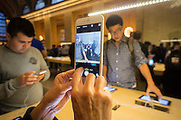 A customer in the Apple store in Grand Central Terminal in New York tries out the new iPhone 6 Plus on Tuesday, September 23, 2014.  Apple announced that it had sold 10 million units of its new phones over last weekend, a million more than the last year's iPhone 5 introduction. The iPhone accounts for almost 70 percent of Apple's profits. (© Richard B. Levine)