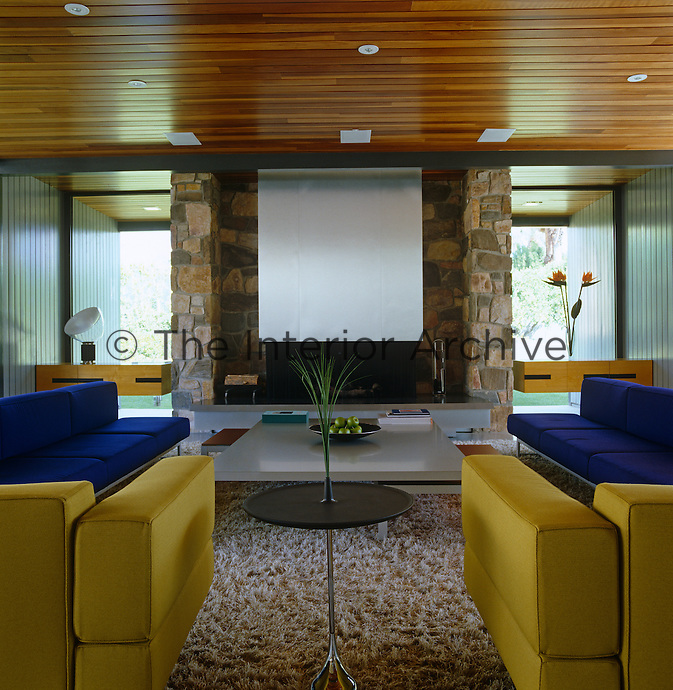 This contemporary living room is furnished with a pair of yellow Piero Lissoni chairs and two contemporary sofas upholstered in blue