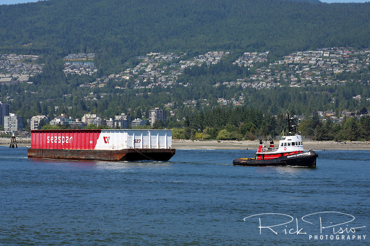 A tugboat pulls a barge through the Lion's Gate in Vancouver, British Columbia