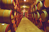 The Disznoko winery in Tokaj: In the underground cellar, rows of wooden barrels piled high with aging Tokaj wine. Workers in the background doing 'batonnage' (stirring of the lees). The Disznoko winery is owned by AXA Millesimes, a French insurance company. Disznoko means pig's head since a big rock in the vineyard supposedly looks like that. The new winery is impressive and a vast amount of money has been invested. Credit Per Karlsson BKWine.com