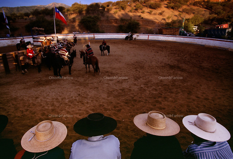 Chilean cowboys dress in traditional Adalusian hats on ponchos. The Hausos (cowboys) topped with flat-brimmed sombreros surround a ring northwest of Santiago to watch competition in the Rodeo InterAsociacional Marga-Marga. They compete in teams called colleras by running a cow out of a pen and pinning it, all while racing against the clock. Huasos wear capes are mantas over a small jacket and their large silver spurs fit into carved wooden stirrups