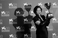 Actress Deanie Yip poses with the Volpi Cup for best actress she received for 'Tao Jie (A simple life)' during a photocall following the award ceremony at the 68th Venice Film Festival