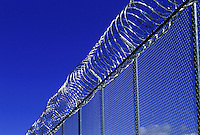 Barbed wire on new exterior prison fence. Western United States.
