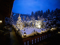A floodlit view of the snow-covered garden and pine forest beyond