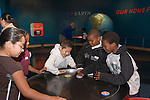 Oakland CA second graders on field trip to Chabot Space and Science Center studying disks floatig on air cushion, prepresenting lack of friction in space