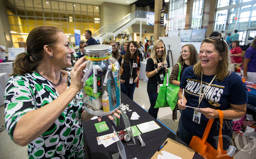 NWA Democrat-Gazette/BEN GOFF @NWABENGOFF<br /> Becky Harrier (left) with Servpro holds up a pitcher full of school supplies as Virginia Rhame (right), a science teacher at Bentonville West High School, writes down her guess on how many items are in the container Friday, Aug. 9, 2019, during the Bentonville Teacher's Fair at Bentonville High School. The person who correctly guesses the number of items in the container wins it. The Greater Bentonville Area Chamber of Commerce holds the event before the start of classes each year to give community businesses and organizations a chance to connect with the approximately 1,800 teachers and administrators in the Bentonville School District. Tuesday is the first day of class in Bentonville schools.