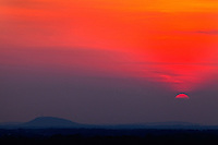 Sunset view from Charlotte NC. Shows the setting sun over an NC foothill mountain.