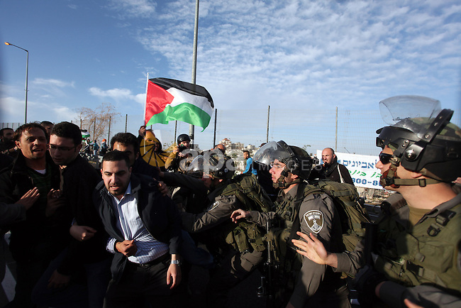 """Israeli soldiers prevent the progress of a symbolic wedding party towards the Israeli constructed controversial separation barrier close to the Israeli manned checkpoint of Hezma in the Israeli occupied West Bank, between Jerusalem and the city of Ramallah on March 9, 2013. The ceremony was organized by Palestinians to denounce what they call the """"racist laws that prohibit the reunification of families"""". In January 2012, the Israeli Supreme Court endorsed a law banning Palestinians married to Israeli Arabs from obtaining Israeli citizenship or residing in Israel. Photo by Issam Rimawi"""