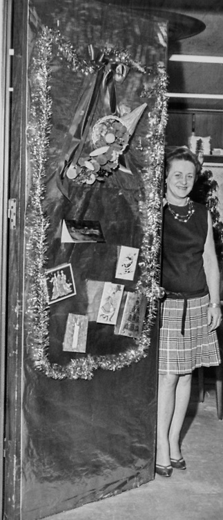 Staff standing behind decorated Congressman's office door during Christmas contest. (Photo by CQ Roll Call via Getty Images)