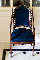 A gothic hall armchair is upholstered in royal blue velvet