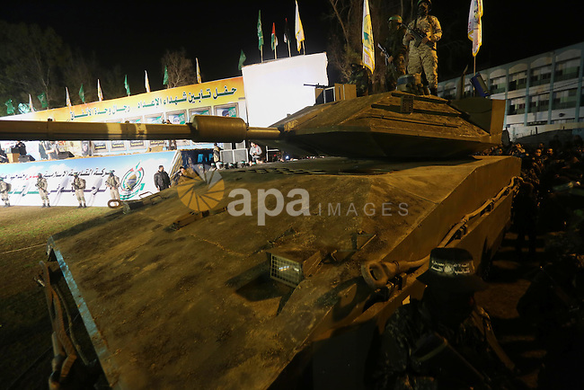 Palestinian members of the Ezzedine al-Qassam Brigades, the armed wing of the Hamas movement, gather around a mock Israeli tank on January 31, 2016 in Gaza city during a gathering to pay tribute to the brigade's militants who died after a tunnel collapsed in the Gaza Strip. Seven Hamas militants were killed on January 28, 2016 after a tunnel built for fighting Israel collapsed in the Gaza Strip, highlighting concerns that yet another conflict could eventually erupt in the Palestinian enclave. Photo by Mohammed Asad