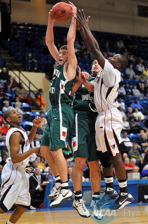 21 MAR 2009: Washington University - St. Louis players Aaron Thompson and Zach Kelly (green) battle Richard Stockton College's Kai Massaquoi for possession of a rebound during the 2009 NCAA Division III Men's Basketball Championship held at the Salem Civic Center in Salem, VA. Washington University - St. Louis defeated Richard Stockton College 61-52 to win their second national title game in a row. Andres Alonso/NCAA Photos.