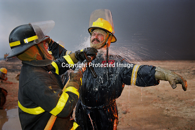 Wayne de Champs, a fire fighter from Calgary, Canada cools off after putting out oil fires on August 13, 1991. He worked at Greater Burhan oilfield in Kuwait. When the Gulf War ended in February 1991, the Iraqi forces retreated and hundreds of wells were blown up. Expert teams mainly from USA and Canada arrived and the last fires were put out in October 1991.
