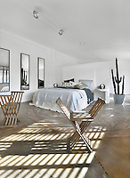This large airy bedroom is simply furnished and features a concrete floor decorated with motifs