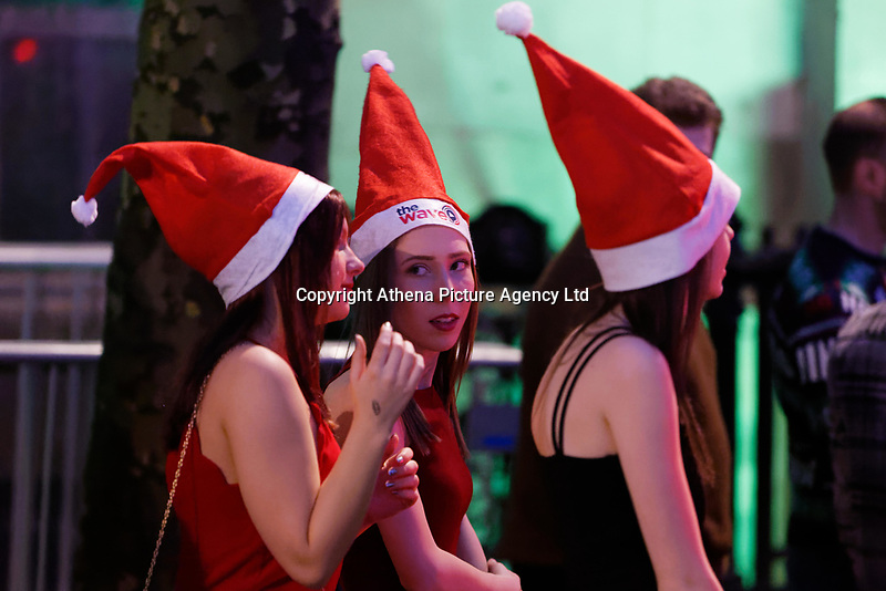 Three young women in Santa hats in Wind Street, Swansea, Wales  on Mad Friday, Booze Black Friday or Black Eye Friday, the last Friday night before Christmas Day, when traditionally people in the UK go out to celebrate the start of their holidays. Friday 22 December 2017