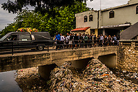 The funeral processsion including friends and family attend the funeral of Carlos, 26, who died from a fever, enters the Grand Cemetery on November 11, 2017 in Port-au-Prince, Haiti. Like the country itself, Burial Road stretches between those who have everything and those with nothing. Even modest funeral parlors offer elaborate services starting at $1,100 — far beyond the means of most Haitians, who live on $2 a day or less. Death is a particularly plentiful resource here. Haitians' life expectancy is only 63.4 — almost 12 years below the Latin America and Caribbean average.<br /> <br /> The funeral homes offer many packages to mourners. The most ornate service comes with a limousine and bus for guests. It runs around $8,000. Few in Haiti have that kind of money. Most take a cheaper option, which still includes professional photos, a hearse, flowers and a small brass band called a fanfa to serenade the corpse in its open coffin and lead the procession to the cemetery.<br /> <br /> Even with the cheapest option, many poor people go into debt to pay for a loved one's funeral. Others opt for shame rather than crippling debt, and never go through with the service. The Louises have always had a problem of customers abandoning their loved ones in their cold rooms.<br /> Photo Daniel Berehulak for The New York Times
