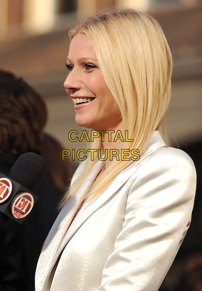 GWYNETH PALTROW.The Marvel World Premiere of Iron Man 2 held at The El Capitan Theatre in Hollywood, California, USA..April 26th, 2010      .half length white shiny jacket blazer black profile interview microphone  smiling .CAP/RKE/DVS.©DVS/RockinExposures/Capital Pictures.