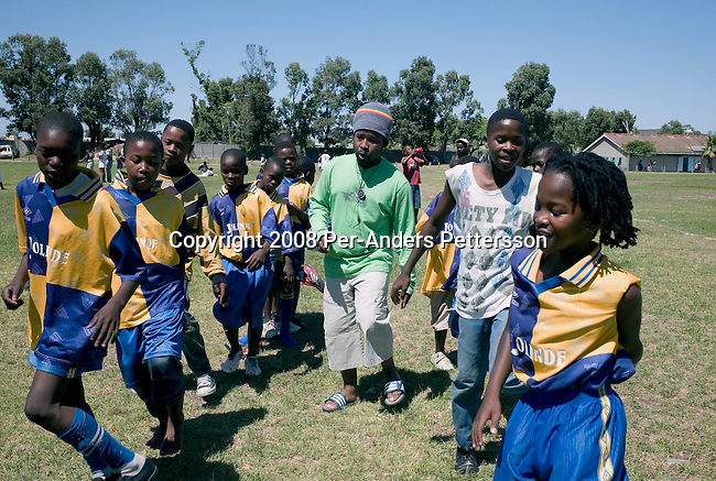 CAPE TOWN, SOUTH AFRICA - FEBRUARY 17: Coach Piet Skosana (c), age 48, leads his youth soccer team warm up before a game on February 17, 2008 in Langa, a poor township outside in Cape Town, South Africa. Mr. Skosana is a construction worker at the newly constructed Green Point stadium in Cape Town. The stadium will host games during the World Cup Soccer tournament when held in South Africa in June 2010. Many young boys from the poor townships dream about being professional soccer players. (Photo by: Per-Anders Pettersson Reportage by Getty Images)..
