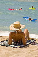 A woman sunbathes on Waikiki beach as vactioners enjoy the refreshing water while floating on colorful rafts.