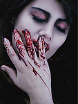 Close-up portrait of a woman with her eyes closed touching her face with her hand with blood dripping through her fingers.