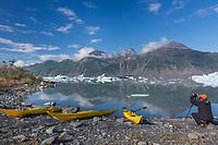 Photographer on a beach in Bear Glacier Lagoon, Kenai Fjords National Park, southcentral, Alaska.