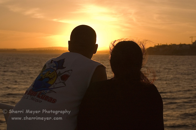 Couple watching the sunset during a sunset dinner cruise, Cabo San Lucas, Baja California, Mexico.