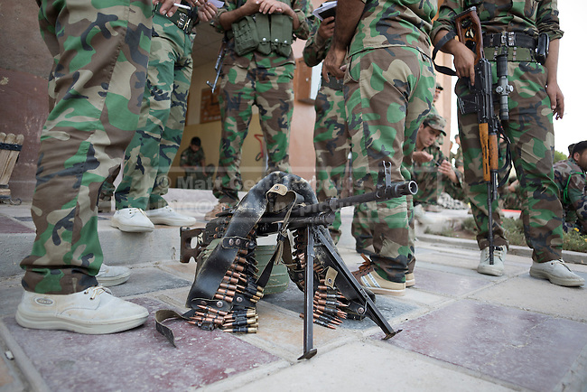30/06/2014. Khanaqin, Iraq. A PKM machine gun is seen amongst peshmerga fighters at a Kurdish peshmerga base in Khanaqin, Iraq, as they prepare to head out and relieve troops at the front line in Jalawla at a Kurdish peshmerga base in Khanaqin, Iraq. Counted by Kurds as part of their homeland, fighting in the town of Jalawla now consists of occasional skirmishes and exchanges of fire between snipers and heavy machine guns on both sides.<br /> <br /> The peshmerga, roughly translated as those who fight, is at present engaged in fighting ISIS all along the borders of the relatively safe semi-automatous province of Iraqi-Kurdistan. Though a well organised and experienced fighting force they are currently facing ISIS insurgents armed with superior armament taken from the Iraqi Army after they retreated on several fronts. &copy; Matt Cetti-Roberts