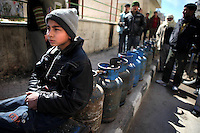 SYRIA, 02.2012, Idlib, Idlib province. © Timo Vogt/EST&OST. A boy sitting on empty gas bottles lined up waiting for gas supply. Many towns suffer from lack of fuels.