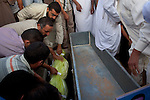 Family members place the body of Khaled Ali Abel Kasm Mussa, 29, in a tomb during the burial of eight bodies found last week in a mass grave near the town of Al-Qala in the Nefusa Moutains, Libya, Friday, Sept. 30, 2011. The eight were reburied next to 35 bodies found in a separate mass grave in the area. Members of the Amazigh indigenous tribe, the men were arrested from their homes and at checkpoints by pro-Gaddafi forces, imprisoned, and finally executed sometime in June. The men, many of them related as fathers and sons, or as brothers, were missing until the first, larger mass grave was found in mid-August.