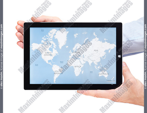 Person hands holding Microsoft Surface Pro 3 tablet computer with world map on its display isolated on white background