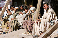 Pakistani men sit together in earthquake devastated village of Pattika, Pakistan