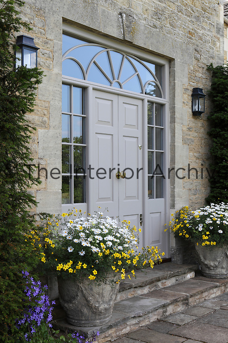 Overflowing containers of white daisies, yellow wild flowers and clusters of purple periwinkle flank the entrance to the house