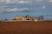 Near the remains of the ancient Egnazia (Fasano), a beautiful old house in the countryside, with a tilled field in foreground and the sea just visible on the background, under a partially clouded sky. Digitally Improved Photo.